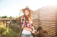 Cheerful smiling cowgirl preparing horse saddle for a ride Stock Photos
