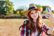 Smiling woman cowgirl taking selfie with mobile phone on ranch Stock Photos