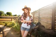 Joyful redhead young cowgirl preparing saddle for riding horse Stock Photos