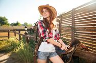 Happy redhead woman cowgirl preparing saddle for riding horse Stock Photos