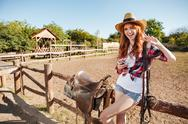 Happy young woman cowgirl with cell phone showing peace sign Stock Photos