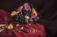 The fruit bowl with grapes and plums against a maroon tablecloth Stock Photos