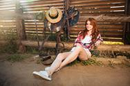 Happy smiling young cowgirl resting at the ranch fence Stock Photos