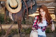 Beautiful redhead young woman cowgirl sitting outdoors Stock Photos