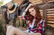 Happy woman cowgirl sitting on farm Stock Photos