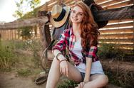 Cheerful young woman cowgirl sitting and smiling outdoors Stock Photos