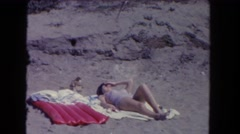 1962: a woman is sunbathing out in the middle of nowhere in the desert Stock Footage