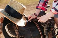Saddle prepared for horse riding by young woman cowgirl Stock Photos