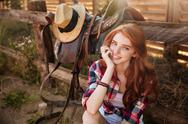 Close up portrait of a happy beautiful redhead cowgirl resting Stock Photos