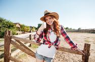 Smiling cheerful redhead cowgirl in hat showing thumbs up gesture Stock Photos