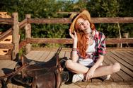 Smiling young woman cowgirl in hat and checkered shirt Stock Photos