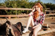 Relaxed woman cowgirl sitting and resting on ranch Stock Photos