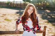 Portrait of pretty redhead cowgirl leaning on the ranch fence Stock Photos