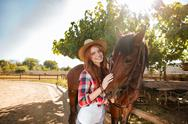 Cheerful young woman cowgirl standing with her horse in village Stock Photos