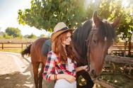 Woman cowgirl standing and taking care of horse in village Stock Photos