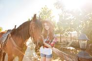Smiling pretty young woman cowgirl in hat with her horse Stock Photos