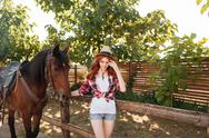 Woman cowgirl walking with her horse in village Stock Photos