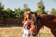 Cheerful young woman cowgirl walking wit her horse on ranch Stock Photos