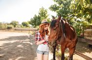 Cute young woman cowgirl taking care and hugging her horse Stock Photos