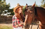 Woman cowgirl taking care of her horse on ranch Stock Photos