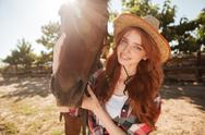 Happy redhead young woman cowgirl with her horse in village Stock Photos