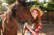Cheerful woman cowgirl in hat with her horse in village Stock Photos