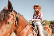 Happy redhead young woman cowgirl smiling and riding horse Stock Photos
