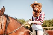 Smiling attrative young woman cowgirl riding horse Stock Photos