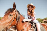 Happy pretty young woman cowgirl riding horse Stock Photos