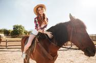 Happy woman cowgirl riding horse on ranch Stock Photos