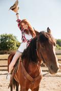 Cheerful woman cowgirl riding horse and having fun Stock Photos
