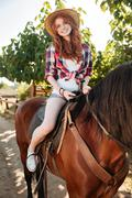 Smiling lovely young woman cowgirl riding horse Stock Photos
