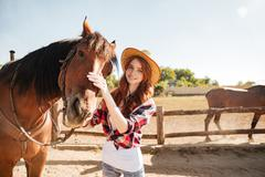 Happy woman cowgirl taking care of her horse on ranch Stock Photos