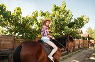 Beautiful redhead young woman cowgirl riding horse in village Stock Photos
