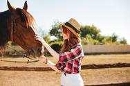Smiling woman cowgirl taking care of her horse on farm Stock Photos