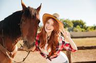 Happy woman cowgirl standing with horse and showing peace sign Stock Photos