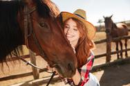 Happy tender young woman cowgirl hugging her horse Stock Photos