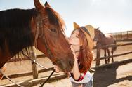 Cute woman cowgirl standing and kissing her horse Stock Photos