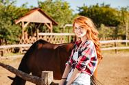 Cheerful attractive young woman cowgirl with horse in village Stock Photos