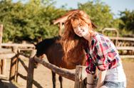 Smiling woman cowgirl sitting on fence in village Stock Photos
