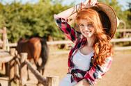 Happy woman cowgirl sitting and smiling on ranch Stock Photos