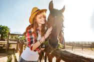 Smiling woman cowgirl taking care and hugging her horse Stock Photos