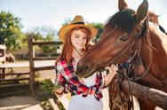 Cheerful woman cowgirl giving food to horse on ranch Stock Photos
