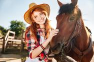 Happy redhead young woman cowgirl in hat with her horse Stock Photos