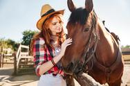 Smiling tender young woman cowgirl with her horse on ranch Stock Photos