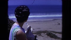 1962: perfectly coiffed lady is commenting on the lovely view from the shore  Stock Footage
