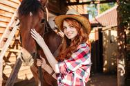 Happy woman cowgirl with her horse in village Stock Photos