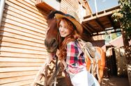 Cheerful woman cowgirl standing and hugging her horse on farm Stock Photos