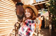Cheerful cute young woman cowgirl in hat with horse Stock Photos