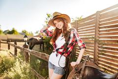 Happy beautiful young woman cowgirl in hat on ranch Stock Photos